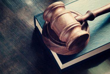 En dommer hammer liggende på en bog
